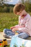 Девушка играя с куклами в луге Стоковая Фотография RF
