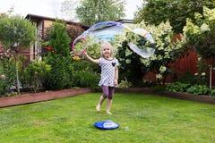 Девушка играя с пузырями мыла в красивом саде Стоковое Фото