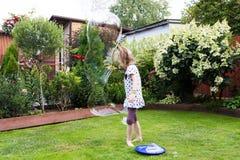 Девушка играя с пузырями мыла в красивом саде Стоковое фото RF