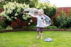 Девушка играя с пузырями мыла в красивом саде Стоковое Изображение