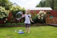 Девушка играя с пузырями мыла в красивом саде Стоковые Изображения
