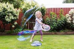 Девушка играя с пузырями мыла в красивом саде Стоковые Изображения RF