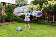 Девушка играя с пузырями мыла в красивом саде Стоковые Фото