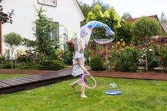 Девушка играя с пузырями мыла в красивом саде Стоковая Фотография RF