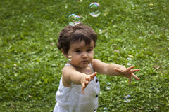 Девушка играя с пузырями мыла в саде Стоковые Изображения RF