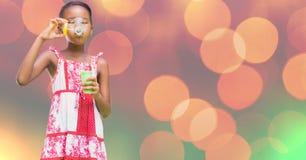 Девушка играя с пузырями мыла против bokeh Стоковое Изображение