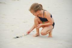 Девушка играя с раковинами моря Стоковое Изображение