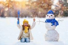 Девушка играя с снеговиком Стоковое Изображение