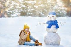Девушка играя с снеговиком Стоковое фото RF