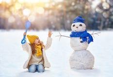 Девушка играя с снеговиком Стоковые Фотографии RF