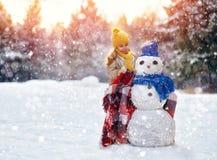 Девушка играя с снеговиком Стоковое Изображение RF