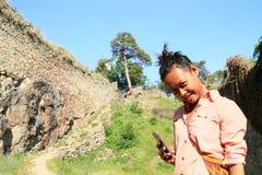 Девушка играя с телефоном на камне девушек замка Стоковое фото RF