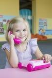 Девушка играя с телефоном игрушки Стоковое Изображение RF
