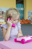 Девушка играя с телефоном игрушки Стоковые Фотографии RF