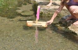 Девушка играя с шлюпкой в воде Стоковые Фото