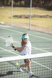 Девушка играя теннис на суде Стоковое Фото