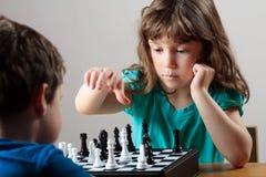 Девушка играя шахмат Стоковые Изображения RF