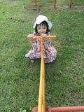 девушка играя seesaw стоковое фото
