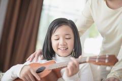 Девушка играя wiyh гавайской гитары ее morther Стоковое Фото