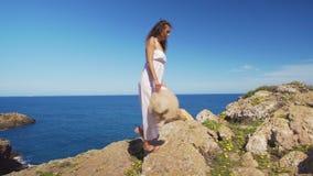 Девушка идет вверх по скале босоногой против голубого моря сток-видео