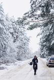 Девушка идет в середине снежной дороги леса стоковые фото