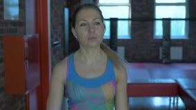 Девушка идет к спортзалу и выправляет ее волосы акции видеоматериалы