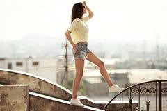 Девушка идет на крышу Город на предпосылке стоковые изображения