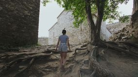 Девушка идет путь в территории старой защитительной крепости вокруг церков в гористых местностях Georgia акции видеоматериалы