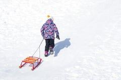 Девушка идя вверх по холму на снеге и вытягивая вверх по ее скелетонам стоковые фото