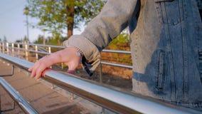 Девушка идя вдоль сияющих рельса и владений дальше к поручню с вашей рукой Славная солнечная погода Конец-вверх женской руки акции видеоматериалы