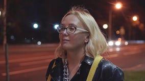 Девушка идя вниз по улице города вечером Проходить автомобили света города сток-видео