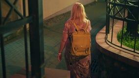 Девушка идя вниз с улицы ночи идет вниз с небольшой лестницы кинематографический сток-видео