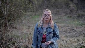 Девушка идя в пустошь с улыбкой смотря камеру Девушка носит белые стекла и голубые куртку джинсовой ткани и a сток-видео