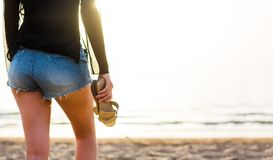 Девушка идя к воде с тапочками в ее руках стоковое изображение