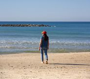 Девушка идя к краю воды моря стоковые фотографии rf
