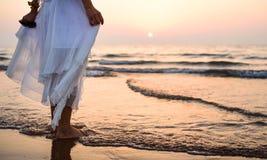 Девушка идя на платье пляжа нося белое стоковые изображения