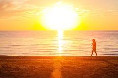 Девушка идя на пляж около моря на заходе солнца стоковая фотография