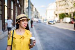 Девушка идя на улицу с кофе для того чтобы пойти стоковое изображение rf