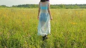 Девушка идя через луг и петли через wildflowers сток-видео