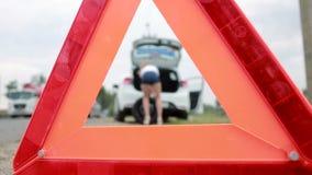 Девушка изменяя прокалыванную автошину на автомобиле ремонт автомобилей на дороге вспомогательную видеоматериал