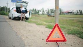 Девушка изменяя прокалыванную автошину на автомобиле ремонт автомобилей на дороге вспомогательную акции видеоматериалы