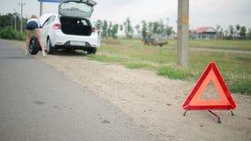 Девушка изменяя прокалыванную автошину на автомобиле ремонт автомобилей на дороге вспомогательную сток-видео