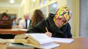 Девушка изучая в библиотеке видеоматериал