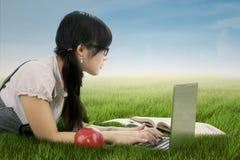 Девушка изучая на траве Стоковая Фотография