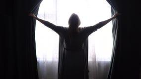 Девушка или женщина в сером купальном халате дома раскрывают занавесы и смотрят в окно видеоматериал
