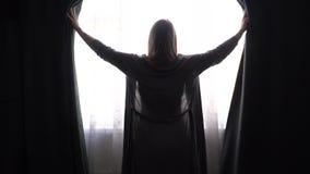 Девушка или женщина в сером купальном халате дома раскрывают занавесы и смотрят в окно акции видеоматериалы