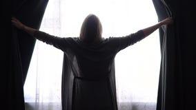 Девушка или женщина на занавесах и взгляде гостиницы открытых темных ых-зелен в окно видеоматериал