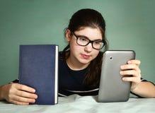 Девушка имеет выбор между книгой и современной пусковой площадкой Стоковая Фотография