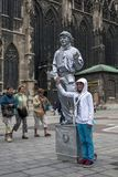 Девушка имеет ее фотоснимок быть принятым при покрашенный уличный исполнитель статуи в серебре в вене в Австрии Стоковая Фотография