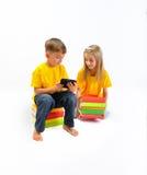 Девушка имеет немного книг, мальчик показывает ей eBook Стоковые Изображения